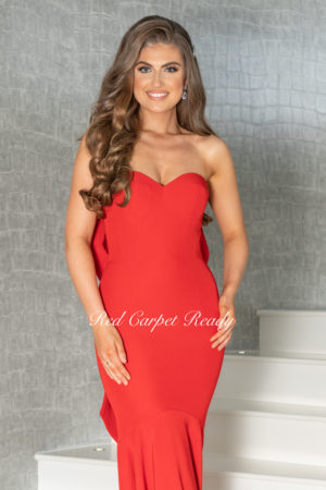 Red bodycon dress with an open back, met with a bow which leeds onto a train.