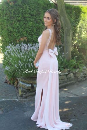 Tight fitting blush pink dress with silver beaded embellishments surrounding an open back, met with a bow leading into a train.