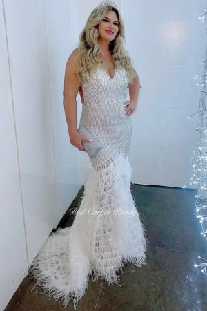 White and silver sleeveless mermaid dress with a feathered train and v-neck.